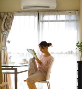 Woman reading comfortably under an AC unit